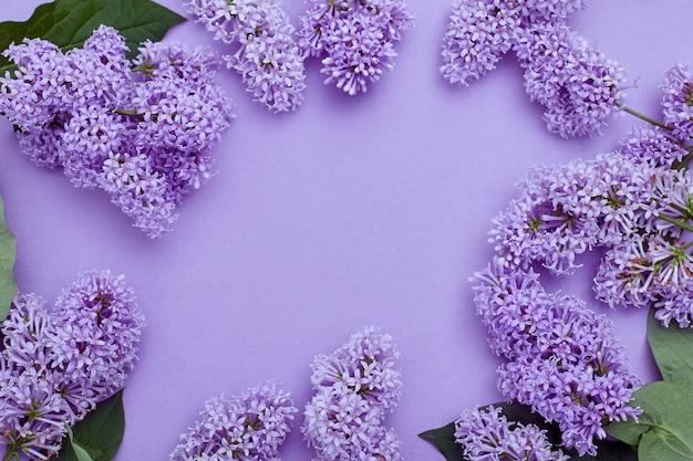 Vista superior de la colocación de flores de color lilas sobre la mesa, ha llegado la primavera, copia espacio superficie morada. flor de lila, cosméticos de primavera para cara y manos