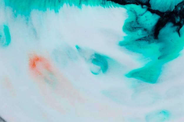 Vista superior del color de agua esparcida en la página en blanco.