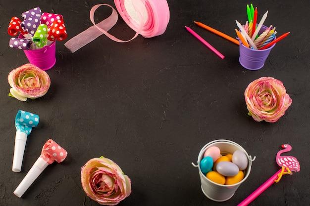 Una vista superior de coloridas decoraciones como dulces, lápices y flores en el escritorio oscuro, decoración de color de cumpleaños