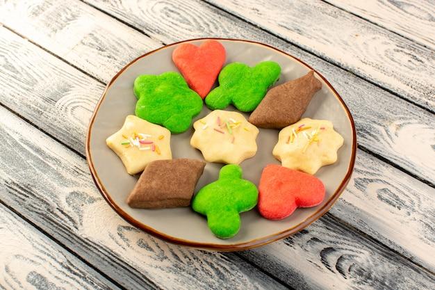 Vista superior de coloridas deliciosas galletas diferentes formadas dentro de la placa redonda en el escritorio de madera gris