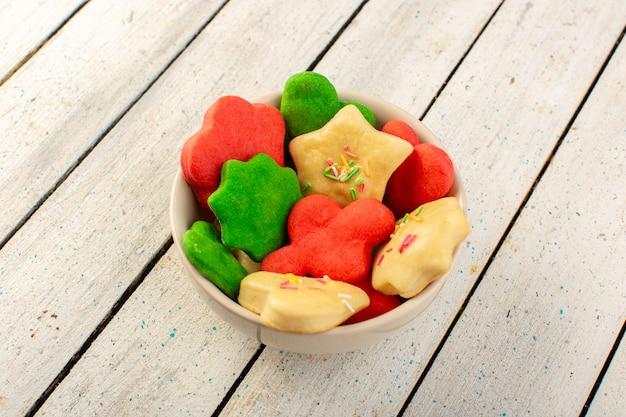 Vista superior de coloridas deliciosas galletas diferentes formadas dentro de la placa redonda en la superficie gris