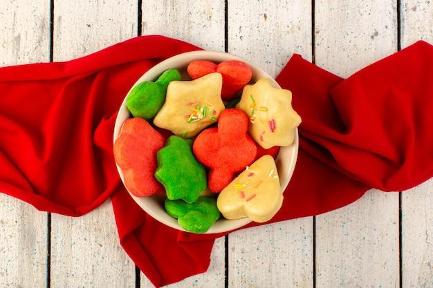 Vista superior de coloridas deliciosas galletas diferentes formadas dentro de un plato redondo con tejido rojo