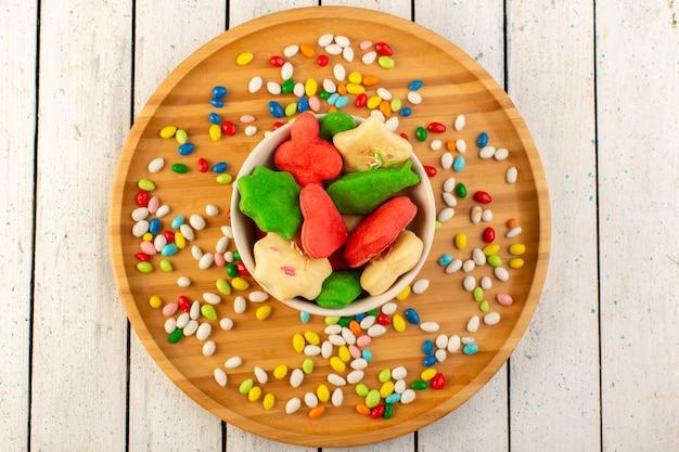 Vista superior de coloridas deliciosas galletas diferentes formadas placa interior multicolor con dulces en el escritorio de madera