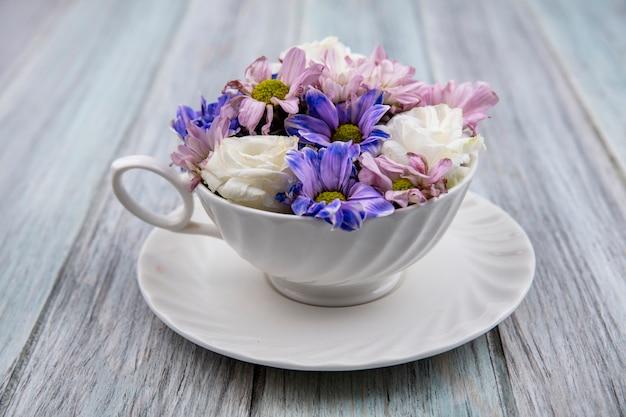 Vista superior de coloridas flores de margarita encantadoras en una taza blanca sobre un fondo de madera gris