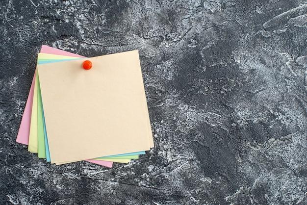 Vista superior de coloridas notas adhesivas con alfiler en superficie oscura