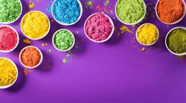 Vista superior del colorido holi en polvo en superficie púrpura