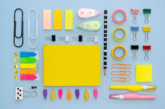 Vista superior de coloridos artículos de papelería de oficina con clips y gomas de borrar