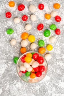 Vista superior de coloridos caramelos dulces repartidos por toda la superficie blanca
