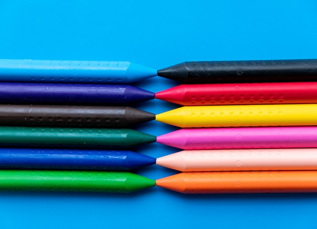 Vista superior coloridos crayones alineados uno frente al otro