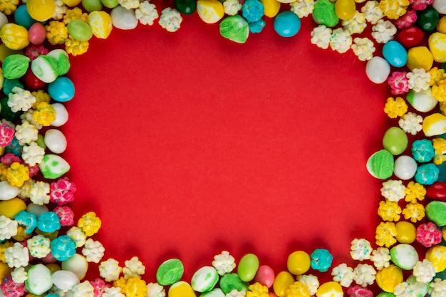 Vista superior de coloridos dulces de azúcar dulce sobre fondo rojo con espacio de copia