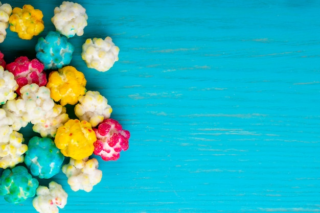 Vista superior de coloridos dulces de azúcar sobre fondo de madera azul con espacio de copia