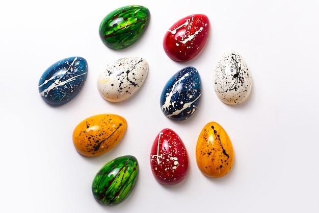 Una vista superior coloridos huevos de chocolate diseñados aislados en la pared blanca