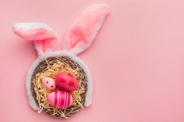 Vista superior de coloridos huevos de pascua en canasta con orejas de conejo y espacio de copia