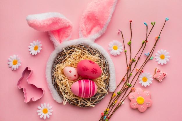 Vista superior de coloridos huevos de pascua en canasta con orejas de conejo y flores de manzanilla