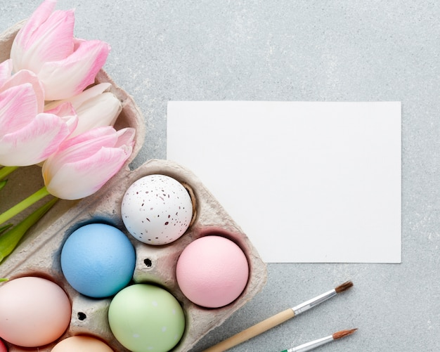 Vista superior de coloridos huevos de pascua en cartón con tulipanes y papel