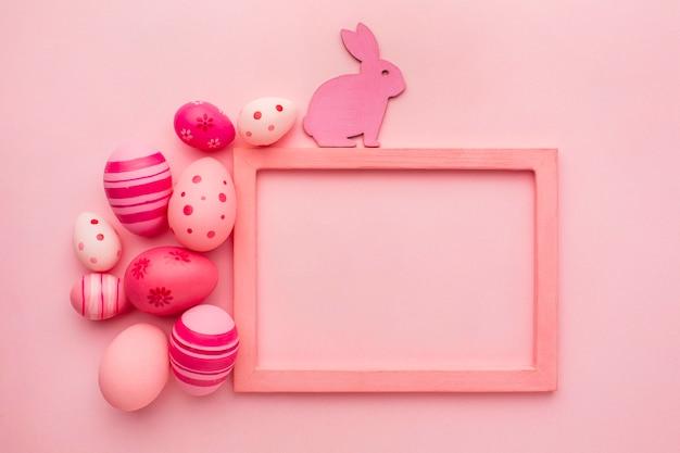 Vista superior de coloridos huevos de pascua con conejito y marco
