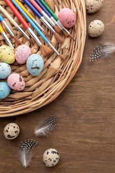 Vista superior de coloridos huevos de pascua con copia espacio y plumas