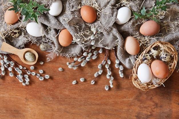 Vista superior de coloridos huevos de pascua y huevos de codorniz, sauces y plumas.