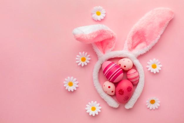 Vista superior de coloridos huevos de pascua con orejas de conejo y flores de manzanilla