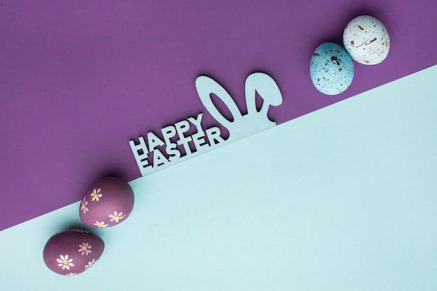 Vista superior de coloridos huevos de pascua con orejas de conejo y saludo
