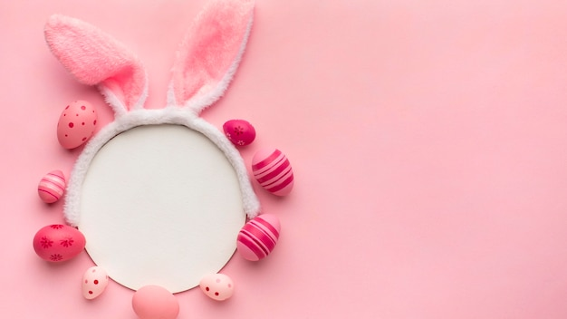 Vista superior de coloridos huevos de pascua con papel y orejas de conejo