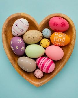 Vista superior de coloridos huevos de pascua en placa en forma de corazón