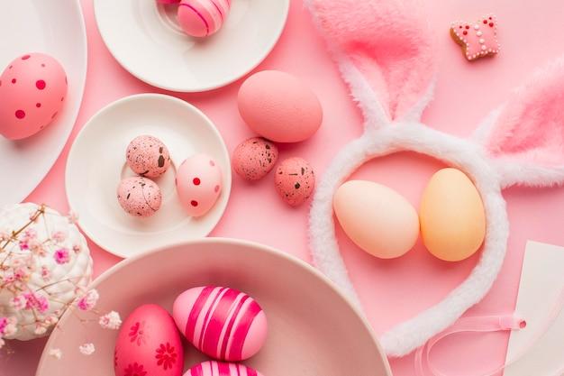 Vista superior de coloridos huevos de pascua con platos y orejas de conejo