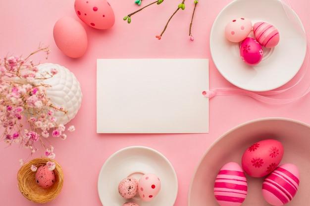 Vista superior de coloridos huevos de pascua en platos con papel y flores