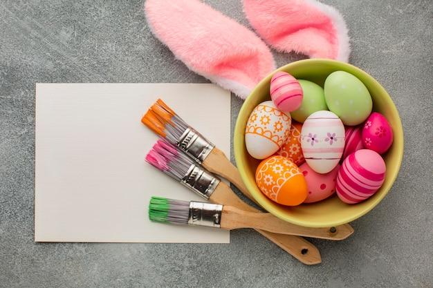 Vista superior de coloridos huevos de pascua en un tazón con pinceles y orejas de conejo