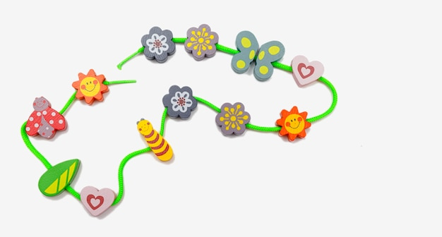 Vista superior con coloridos juguetes de madera para bebés sobre fondo blanco aislado.