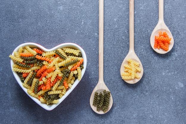 Vista superior coloridos macarrones pasta en un recipiente en forma de corazón y cucharas en la superficie gris. horizontal