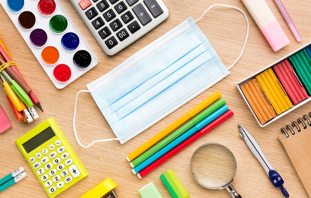 Vista superior de coloridos suministros de regreso a la escuela con máscara médica
