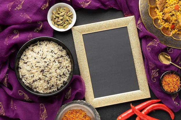 Vista superior de comida india con sari y marco.