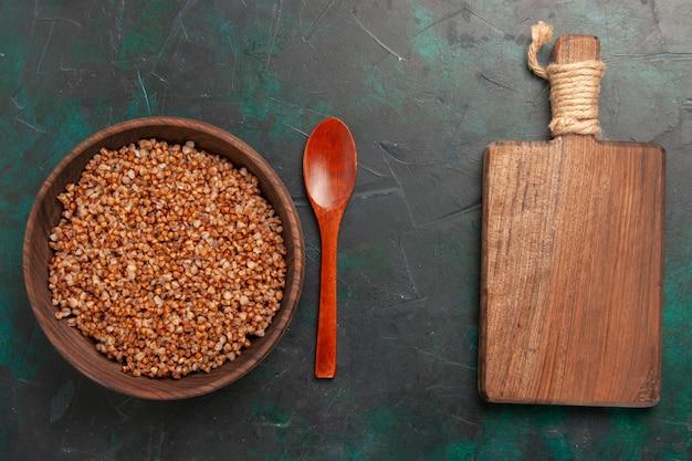 Vista superior de comida sabrosa de trigo sarraceno cocido dentro de la placa de madera marrón sobre la superficie verde oscuro
