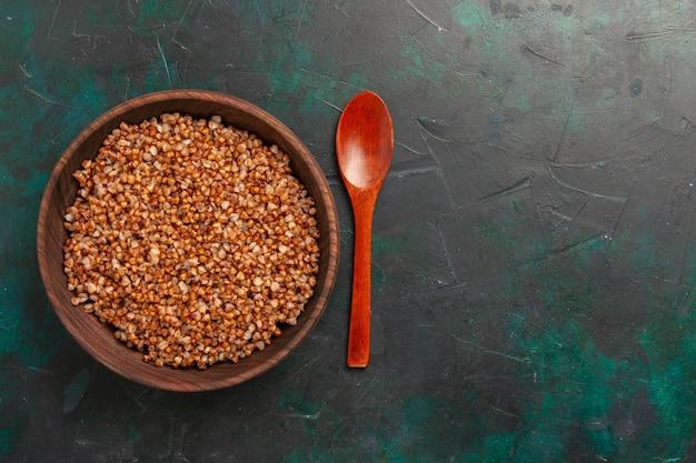 Vista superior de la comida sabrosa de trigo sarraceno cocido dentro de la placa de madera marrón sobre la superficie verde