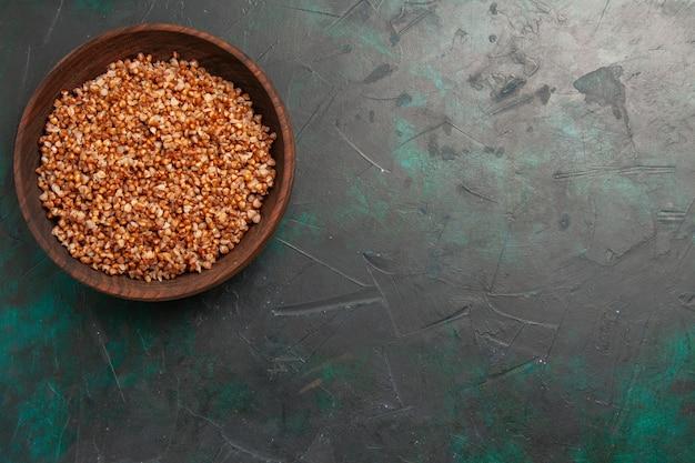 Vista superior comida sabrosa de trigo sarraceno cocido dentro de la placa marrón sobre la superficie verde oscuro