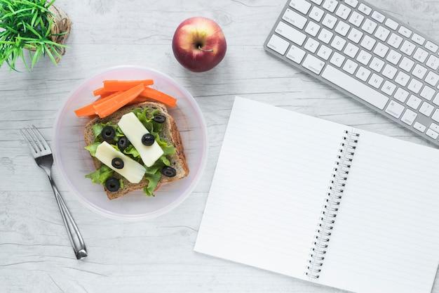 Vista superior de la comida saludable con libro espiral abierto y teclado de computadora inalámbrico en la mesa