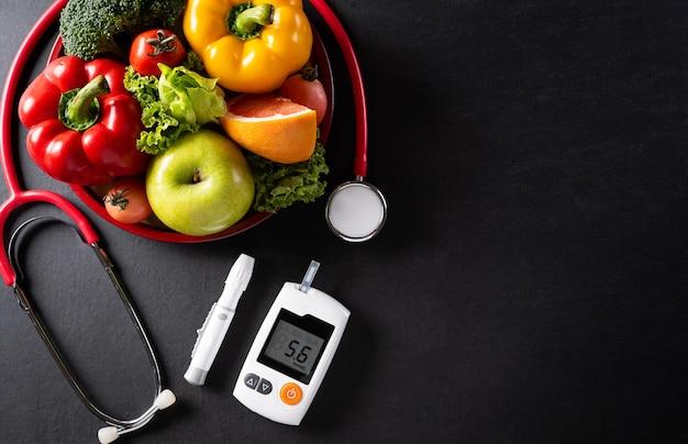 Vista superior de comida sana en plato con estetoscopio y control de diabetes en superficie oscura