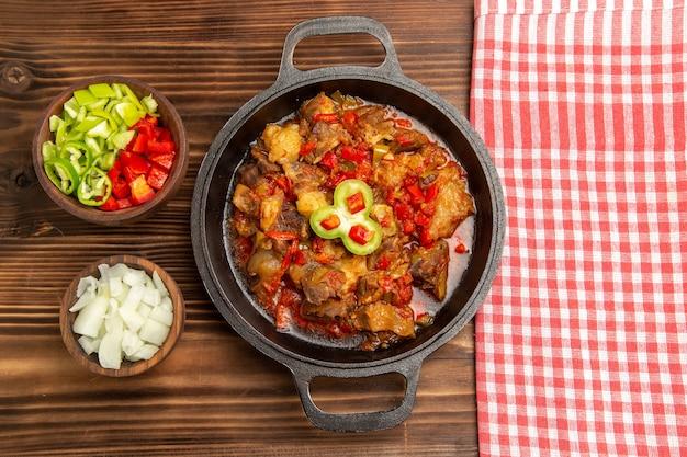 Vista superior de comida vegetal cocida con carne y pimiento en rodajas sobre la superficie de madera marrón