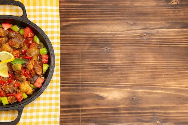 Vista superior de comida vegetal cocida con carne y pimientos en rodajas dentro de la sartén en el escritorio de madera marrón
