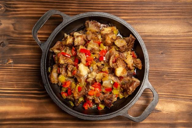 Vista superior de comida vegetal cocida con carne y pimientos en rodajas en el escritorio de madera