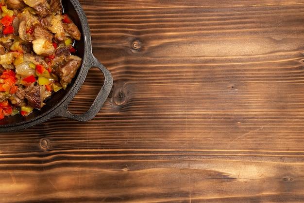 Vista superior de comida vegetal cocida con carne y pimientos en rodajas en la superficie de madera
