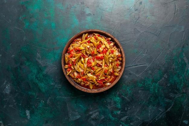 Vista superior de comida vegetal en rodajas cocinada con diferentes ingredientes en el escritorio azul oscuro