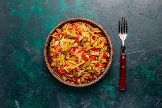 Vista superior de la comida de verduras en rodajas cocinado delicioso plato sobre fondo azul.