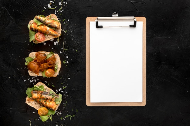 Vista superior de comidas de mariscos con bloc de notas