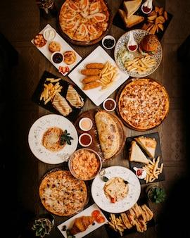 Vista superior comidas sabrosas deliciosas diferentes pasteles y platos en la superficie marrón