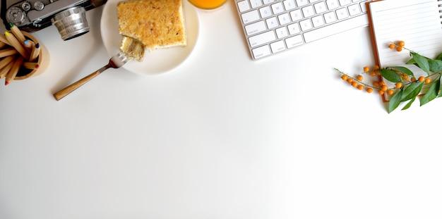 Vista superior del cómodo espacio de trabajo con cámara y desayuno en mesa blanca