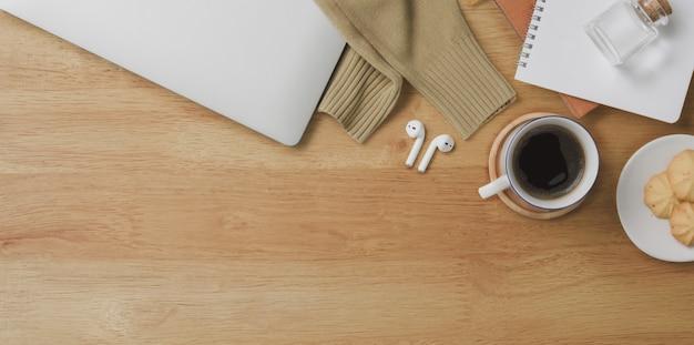 Vista superior del cómodo espacio de trabajo con computadora portátil y suministros de oficina