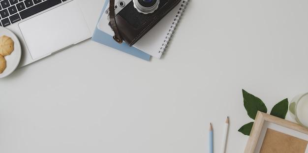 Vista superior del cómodo espacio de trabajo del fotógrafo con suministros de oficina en el fondo de la mesa blanca