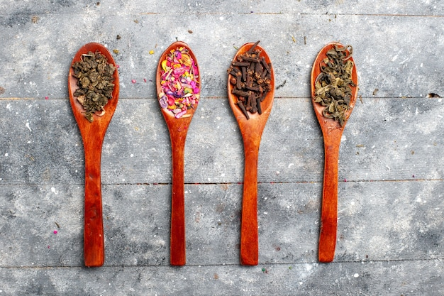 Vista superior de la composición de condimentos de diferentes colores dentro de las cucharas en el color gris de la planta seca del té del escritorio
